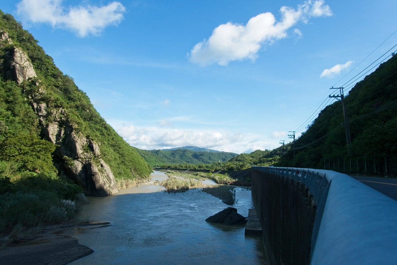 Looking along guard rail - River to the left and down - mountain next to river - blue skies and a few white clouds