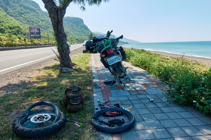 motorcycle on sidewalk without rear tire - ocean to the right - road to the left - tools and tire on the ground behind motorcycle