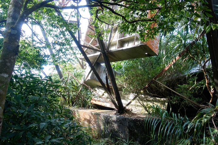 metal structure on top of concrete base - a few metal box-like structures have fallen and one suspended - some tree branches off to side