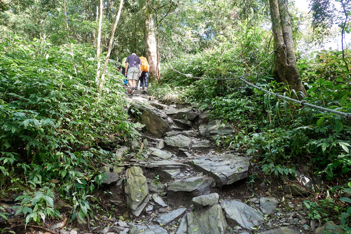 Wide rocky trail - rope on one side and hikers at top