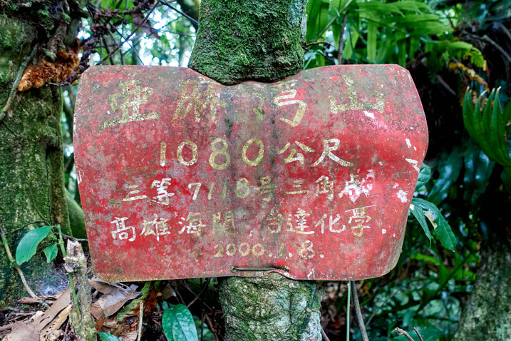 Red sign attached to tree - tree has grown over the sign