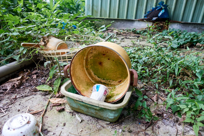 Old plastic bucket and dishware on concrete slab