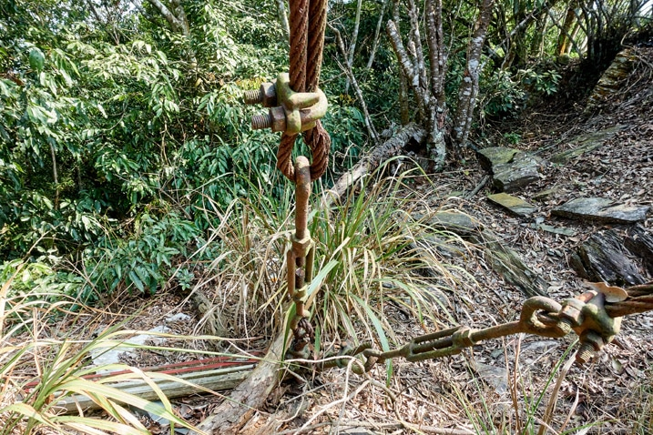 Rusted anchor cables going into ground