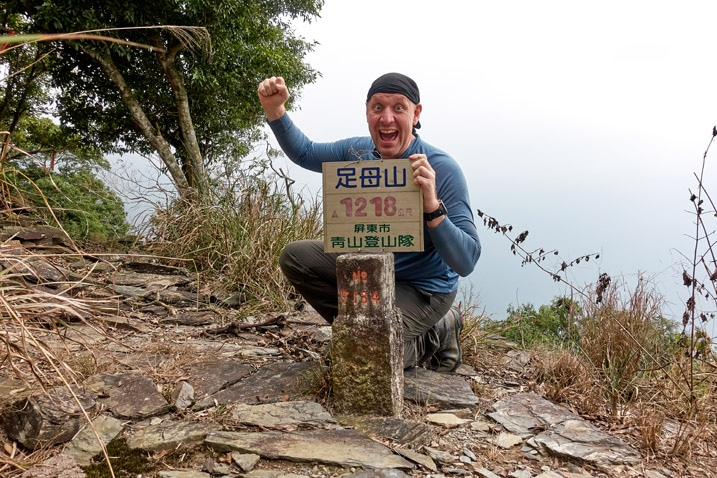 Man posing behind ZuMuShan 足母山 triangulation stone in triumphant pose