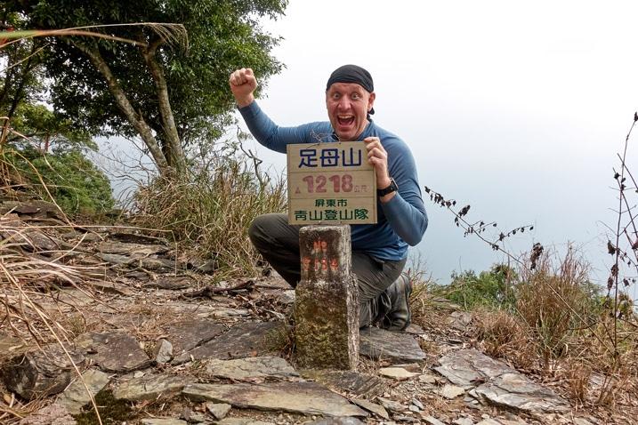 Man posing behind ZuMuShan 足母山 triangulation stone in triumphant pose