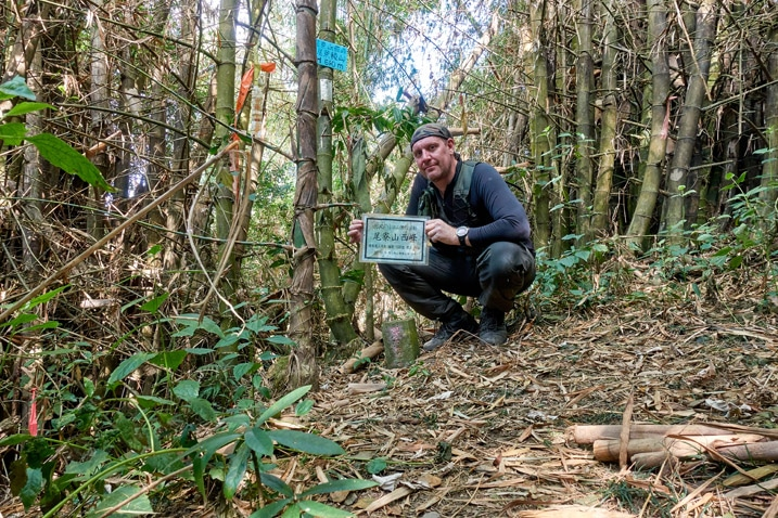 Man standing behind a triangulation stone holding a sign - WeiLiaoShan West peak – 尾寮山西峰
