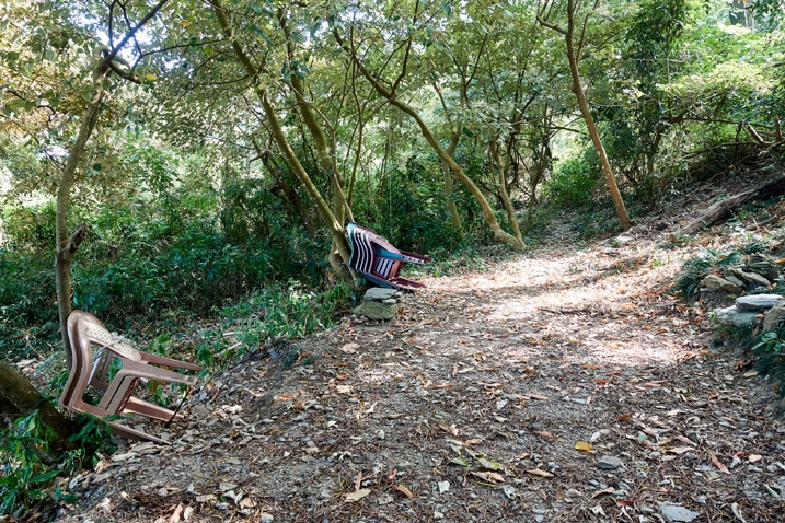 Open dirt area - plastic chairs stacked against a tree - trees in backround - WeiLiaoShan Hike – 尾寮山