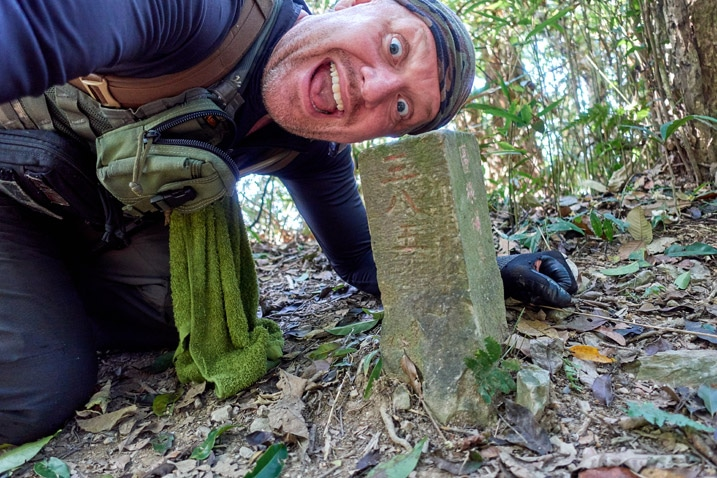 man sideways above triangulaion stone looking happy - WeiLiaoShan Hike – 尾寮山