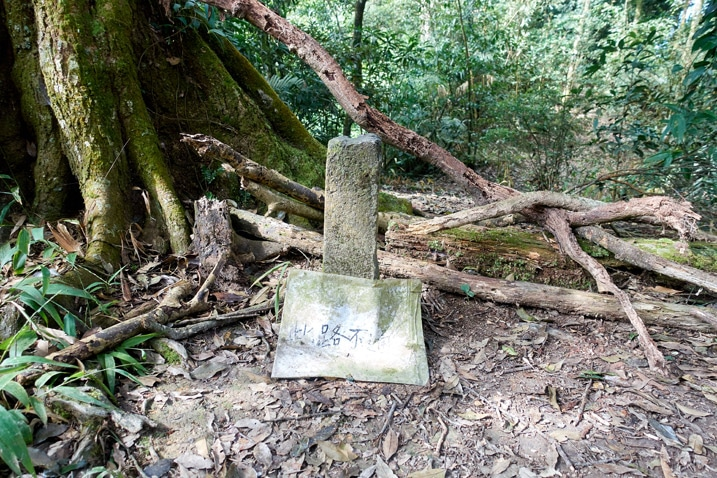 Stone marker with old sign in front of it - tree branches stacked behind it - WeiLiaoShan 尾寮山 trail