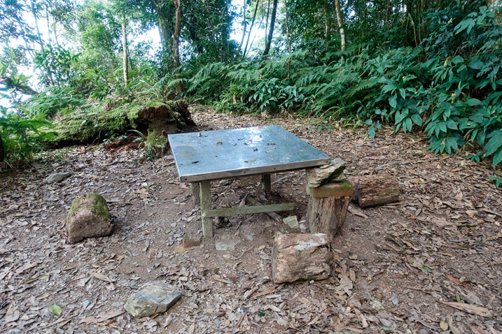 A metal table in the middle of an open area - trees in the background - WeiLiaoShan 尾寮山 trail