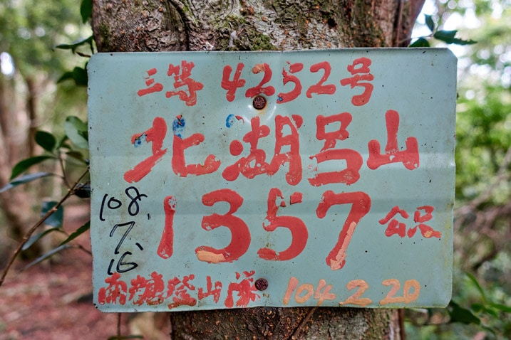 Faded green sign with red lettering in Chinese - BeiHuLuShan Peak 北湖呂山