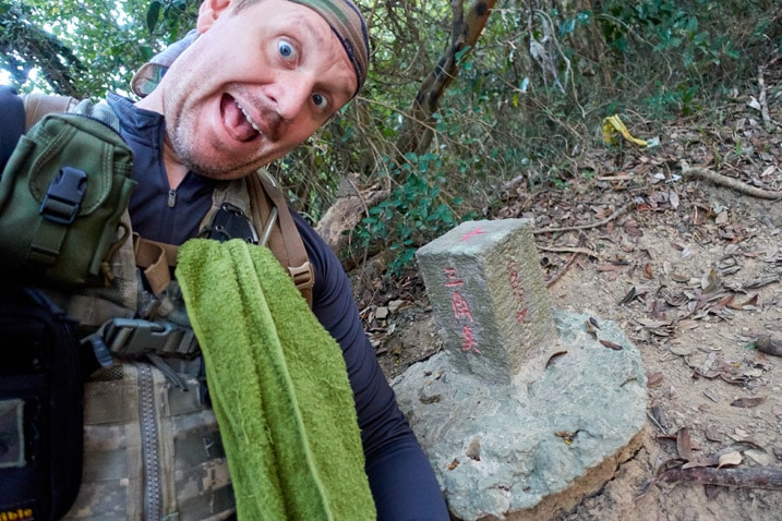 Man posing in front of survey stone for 北旗尾南山