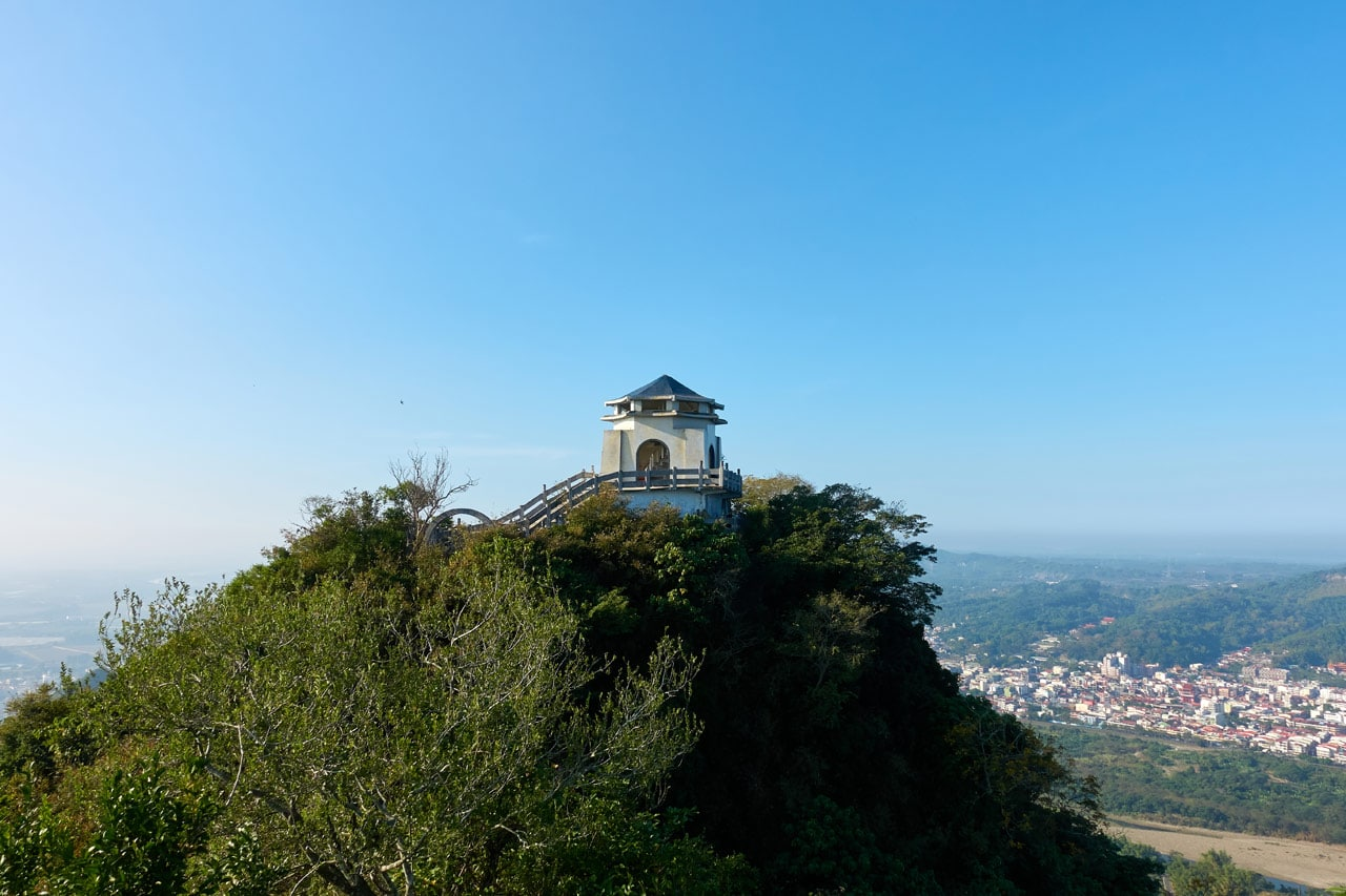 Looking at mountain peak with structure on top - blue skies and city below - 旗月縱走