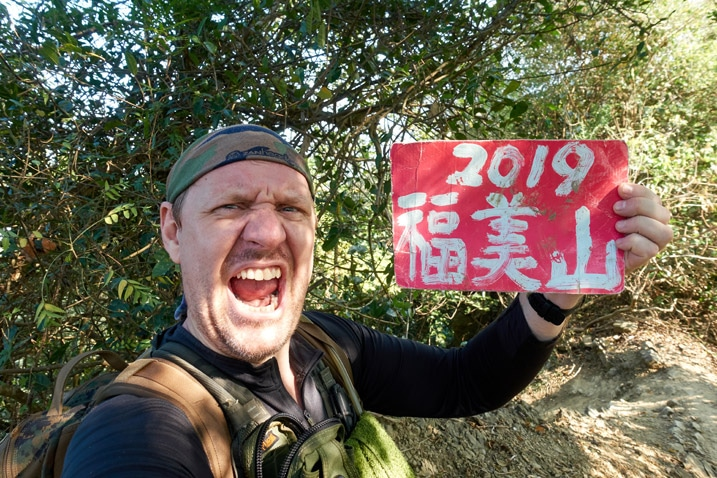 Man in triumphant pose holding sign - 旗月縱走 - 福美山