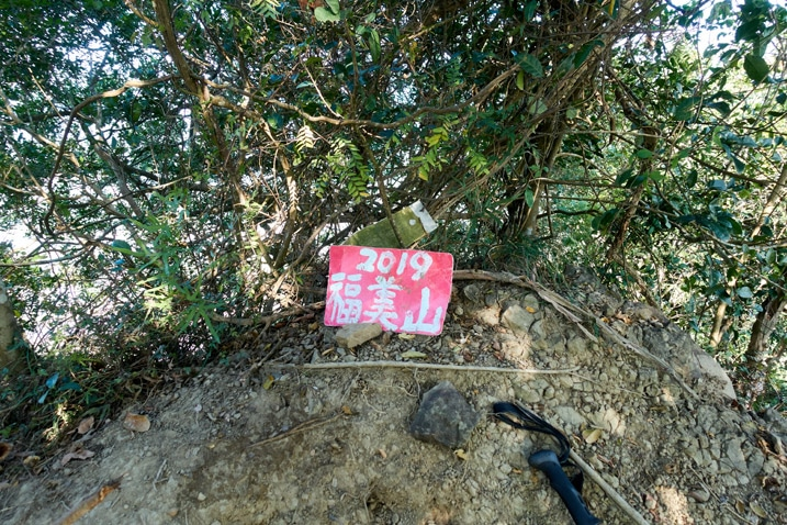 Red sign in Chinese lying on the ground next to hiking pole - 旗月縱走 - 福美山