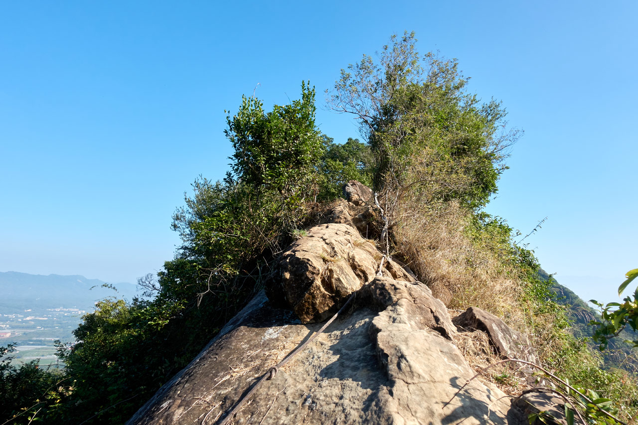 Looking up at steep rockface with rope - 旗月縱走