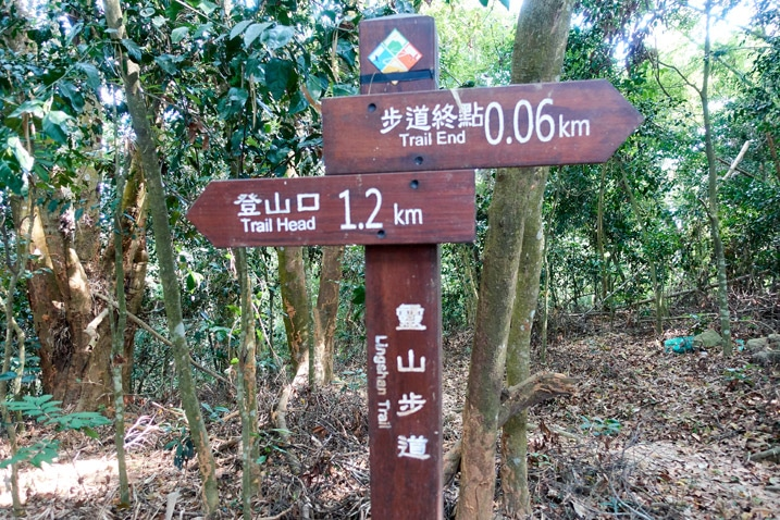 Wooden sign post with signs written in Chinese - 靈山步道 - 旗月縱走