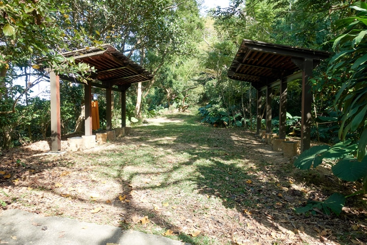 Open dirt and grass area with two covered sitting areas flanking it - 靈山步道 - 旗月縱走