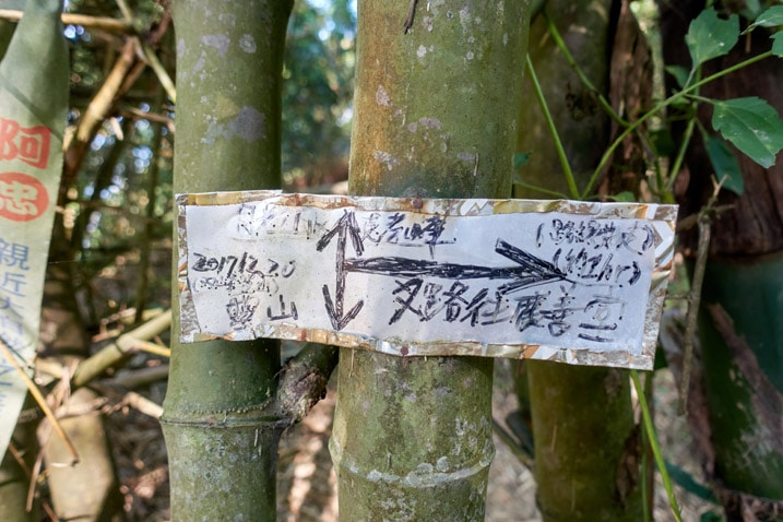 Sign attached to a bamboo tree in Chinese - 旗月縱走