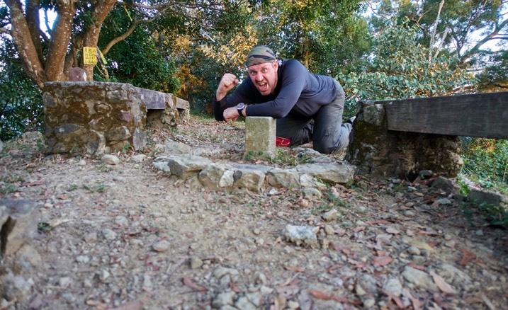 Man leaning behind triangulation stone in triumphant pose - 旗月縱走 - 月光山
