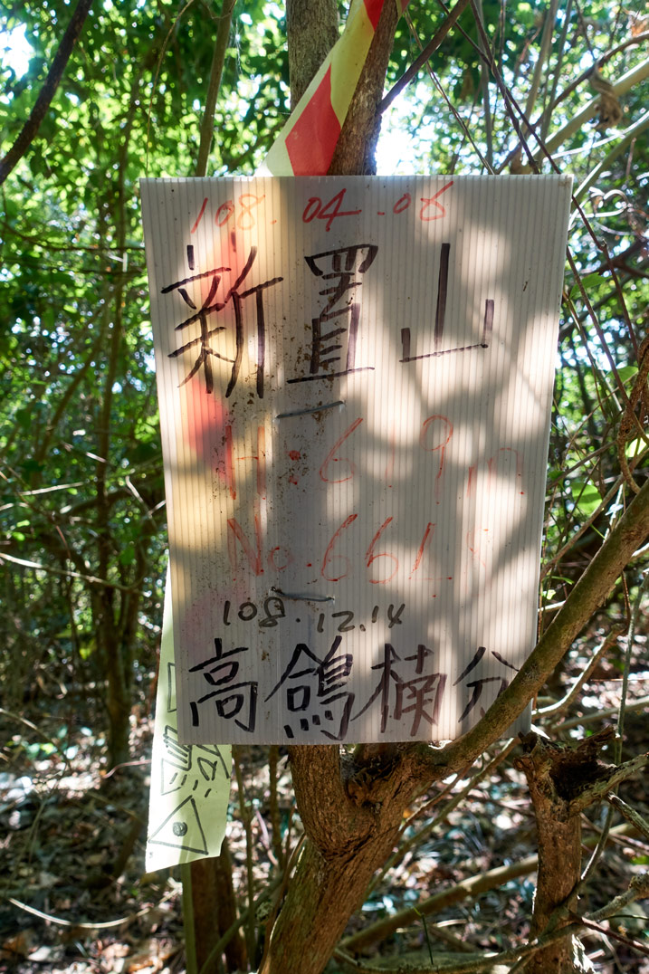 Plastic sign with Chinese writing at XinZhiShan - 新置山 Peak