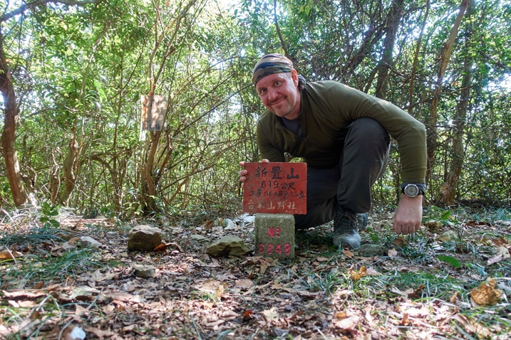 Man standing behind triangulation stone holding sign - XinZhiShan - 新置山 Peak