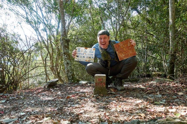 Man posing triumphantly behind a triangulation stone - holding two signs in Chinese