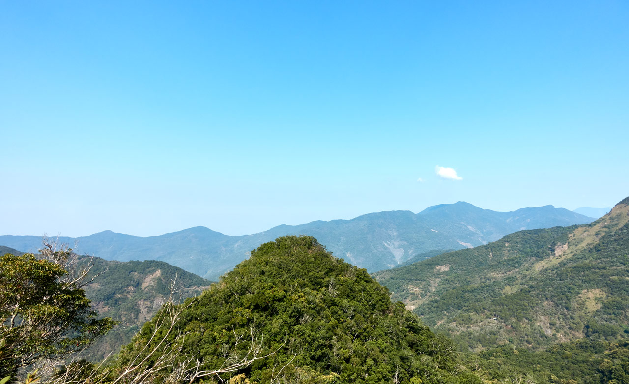 View of mountain peak and mountains beyond - blue sky