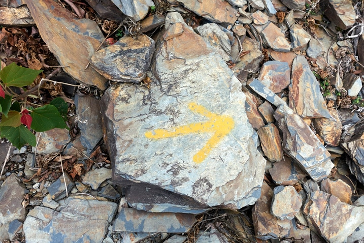 Rock with yellow arror spray painted on it