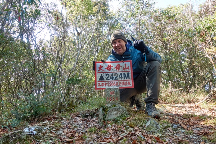 Man standing triumphantly behind 大母母山 Damumushan triangulation stone - holding sign - blue jacket