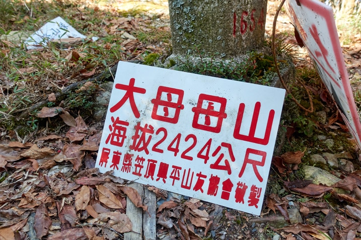 Triangulation stone with white sign with chinese writing on it