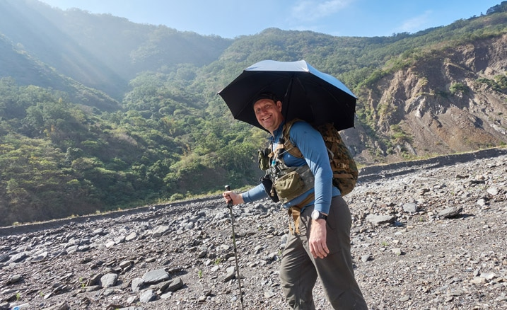 Man standing with umbrella over his head, holding a trekking pole - in rocky riverbed - mountains and blue sky