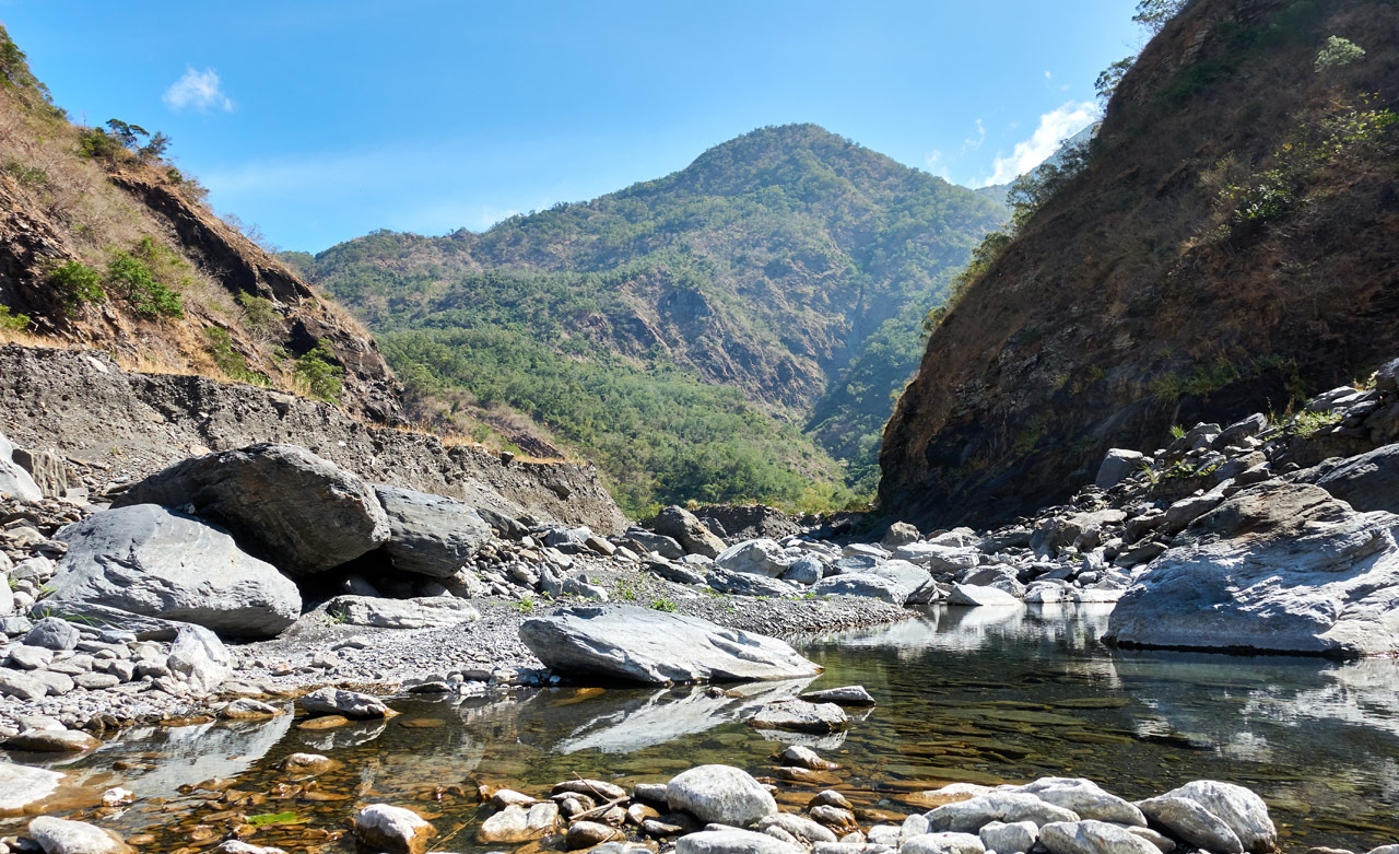 Mountain riverbed pool of water - mountains and blue sky in distance