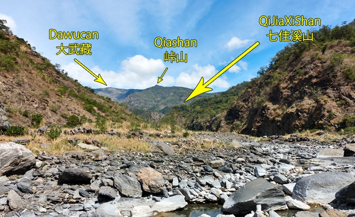 Rocky riverbed with mountain peaks labeled in English and Chinese