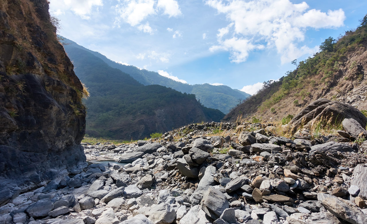 Wide open rocky riverbed with mountains and blue sky