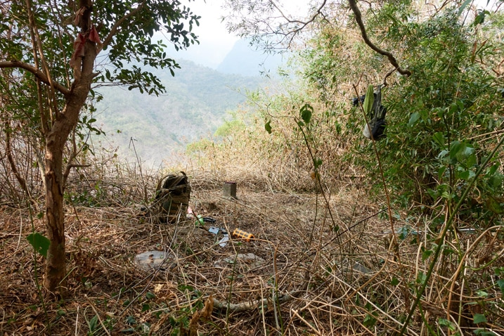 QiJiaXiShan – 七佳溪山 triangulation stone in cleared area - backpack and other items strewn about