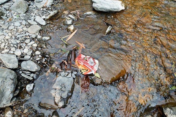 Empty bag of chips discarded in water on riverbed