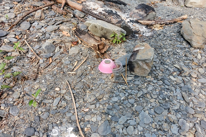 Pink plastic bowl discarded on riverbed