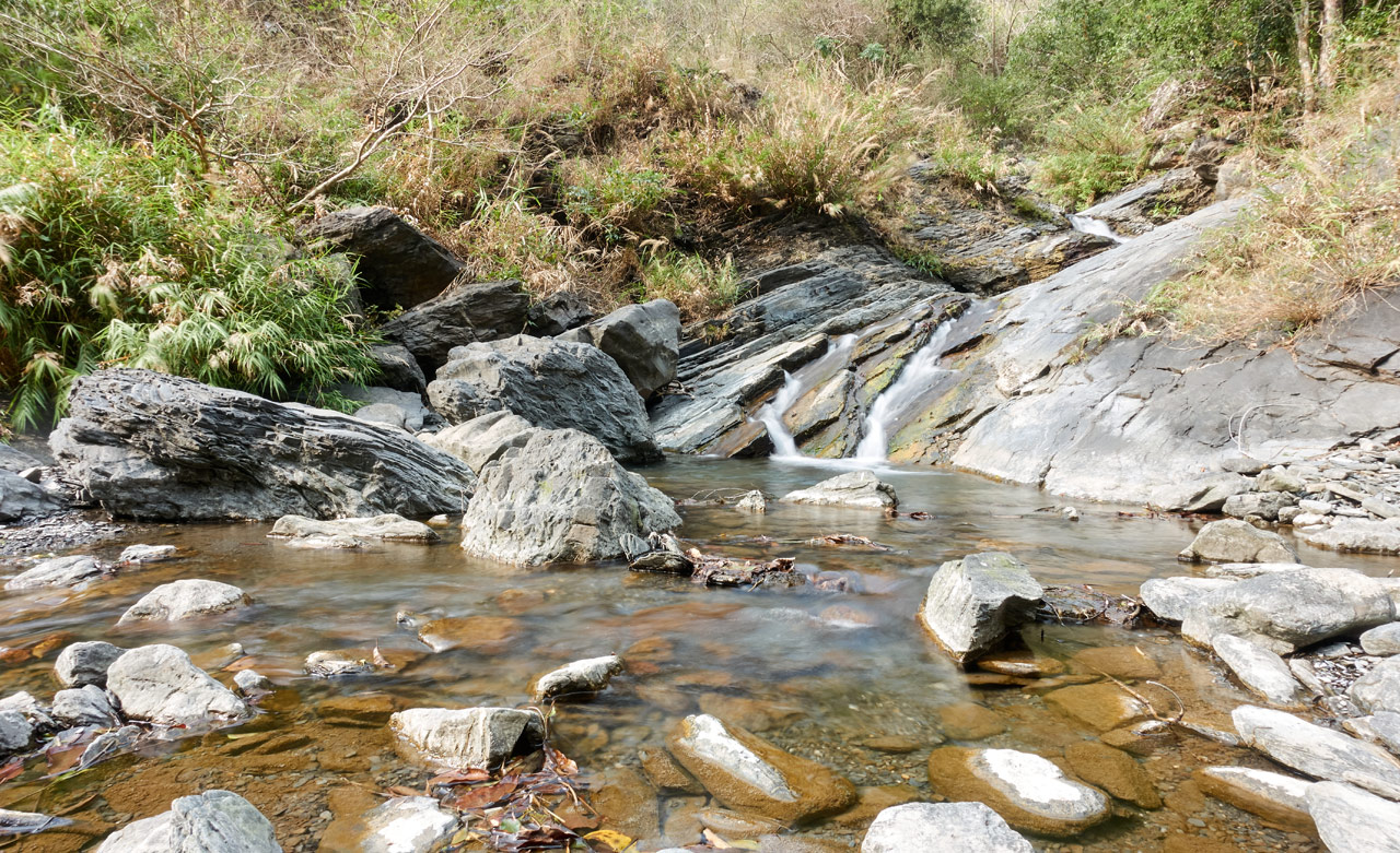 Mountain stream flowing down into small pool of water - many large rocks inside
