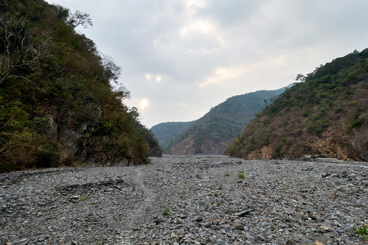 Rocky riverbed with trail - mountains on either side - overcast sky