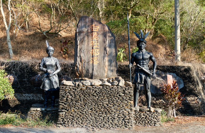 Taiwan aboriginal monument - large stone pillar flanked by aboriginal warrior and female