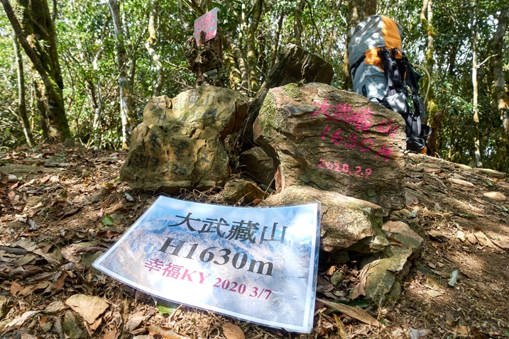 Large stones next to each other with Chinese writing on them - laminated sign with Chinese in front of stones - backpack in the background