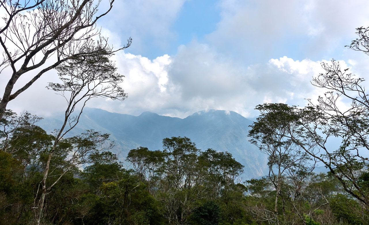 Mountains in distance - mostly cloudy sky with little blue patch - trees in foreground