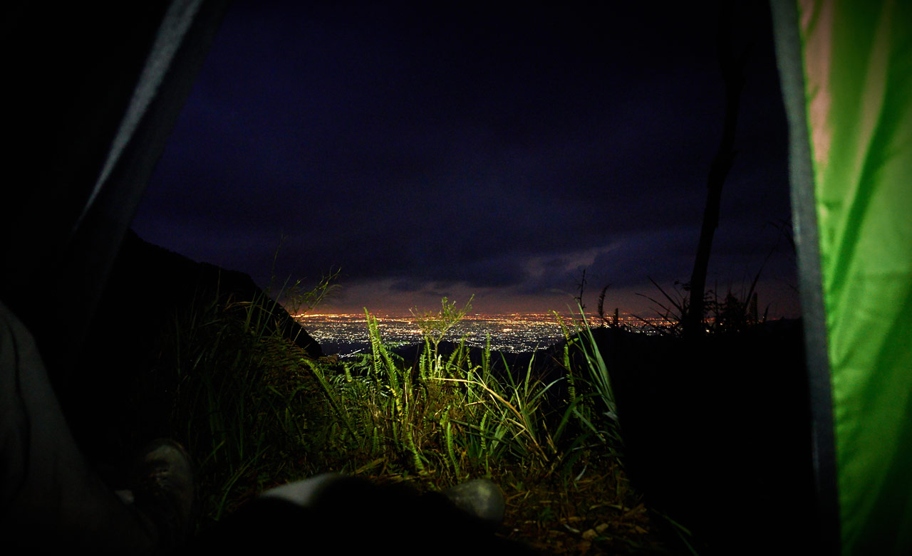 Looking out from tent at city at night - grass in foreground