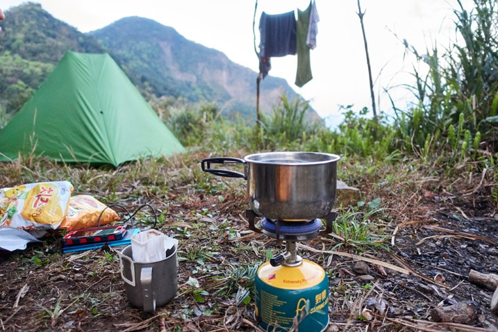 Water boiling on camp stove - tent, clothes hanging, and mountain in background
