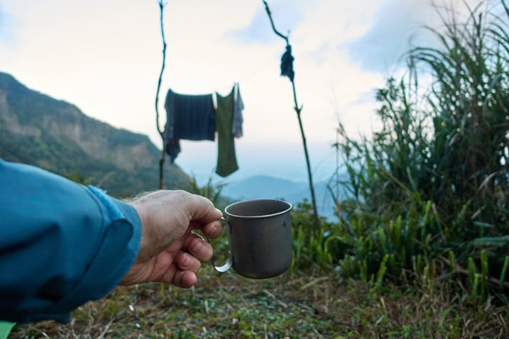Hand holding titanium coffee cup - clothes hanging in background - mountains in distance