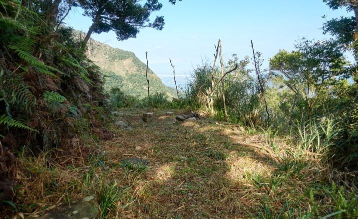 Mountainside hunter's camp - flat open area - mountains beyond - blue sky