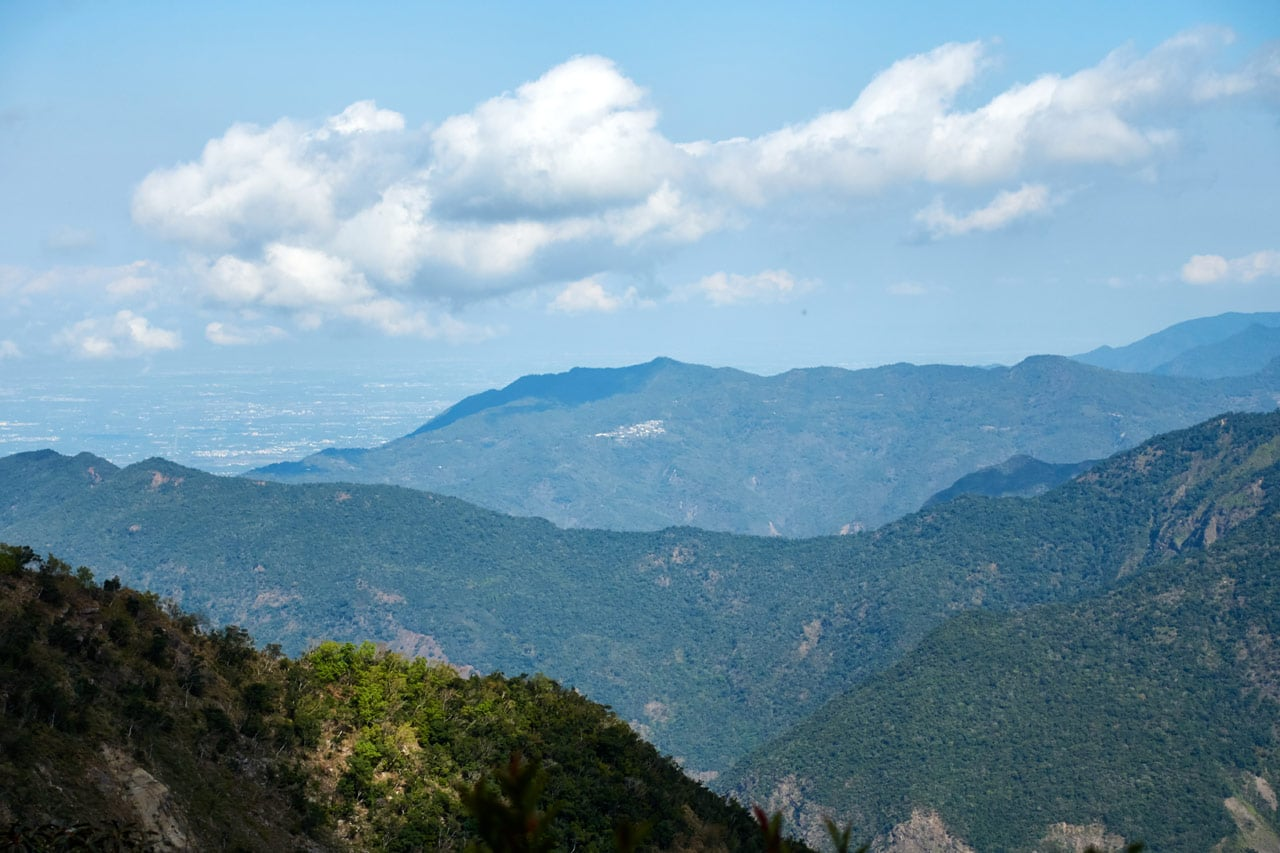 Zoomed in picture of mountains and blue sky with clouds - village nestled on mountainside