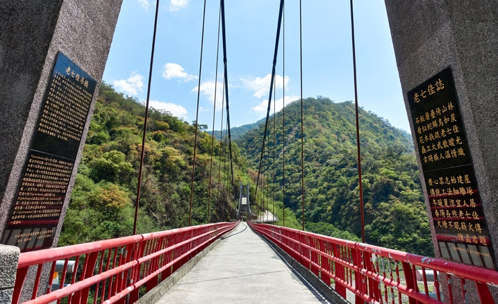 standing on end of suspension bridge looking at other side - mountains behind and blue sky