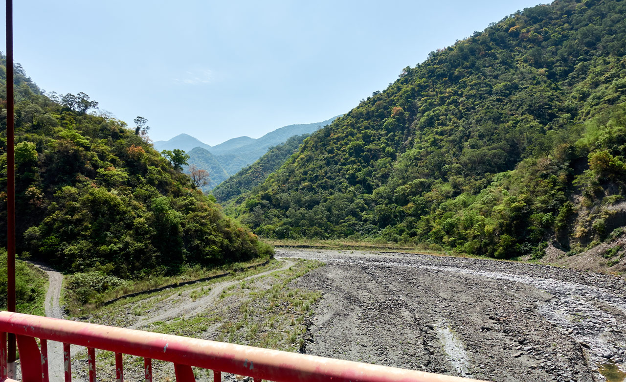 Looking off side of suspension bridge - mountains and riverbed in distance - blue sky - red railing in front